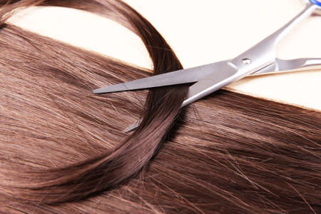 Long brown hair and scissors on wooden background photo