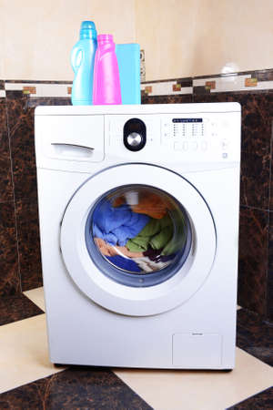 Washing machine loaded with clothes in bathroom Stock Photo