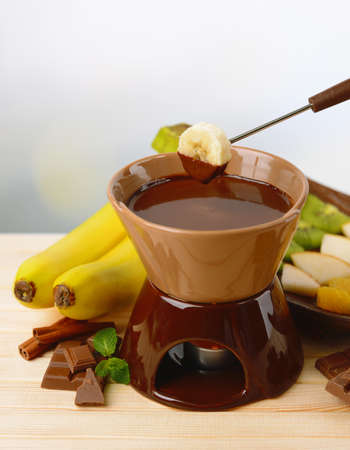 Chocolate fondue with fruits, on wooden table, on light background photo