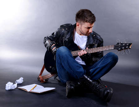 jamming: Young musician playing  guitar on gray background