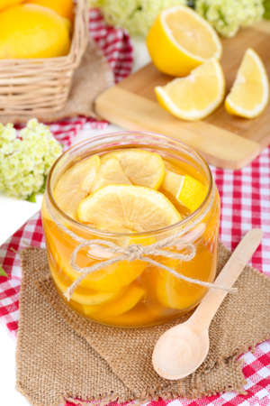 Tasty lemon jam on table close-up photo