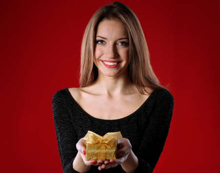 Attractive woman with gift box, on color background photo