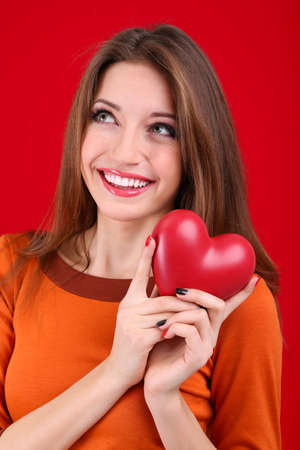 Attractive woman with heart, on red background photo