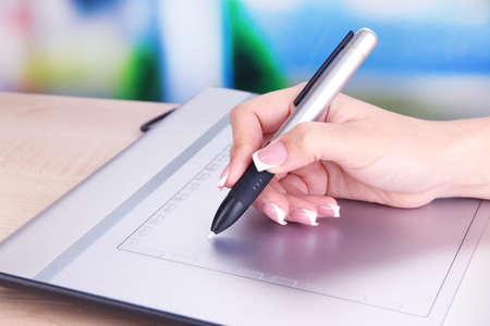 stylus: Female hand using graphics tablet on table on bright background