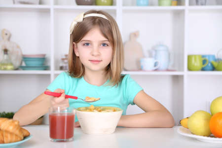 Beautiful little girl eating breakfast in kitchen at home photo
