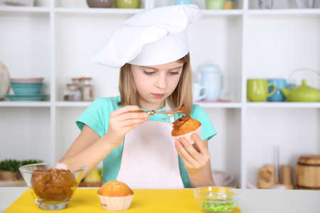home decorating: Little girl decorating cupcakes in kitchen at home