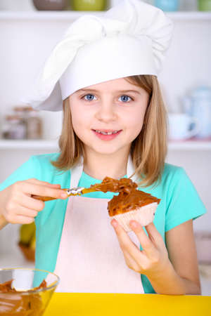 Little girl decorating cupcakes in kitchen at home photo