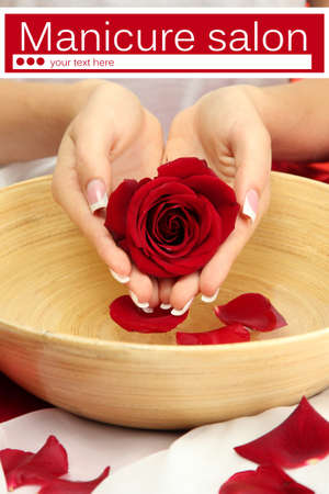 Woman hands with wooden bowl of water with petals close up photo