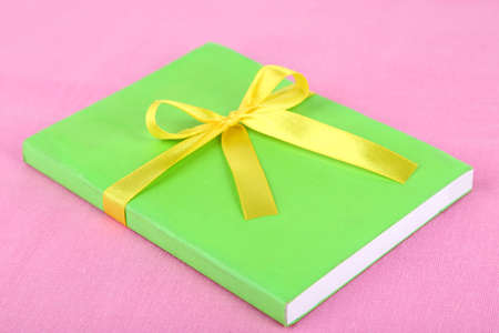 Book wrapped with color ribbon, on color background photo