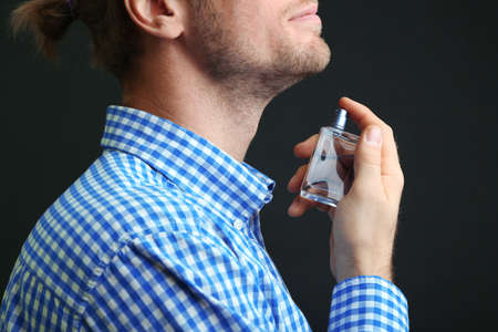 Handsome young man using perfume on black background photo