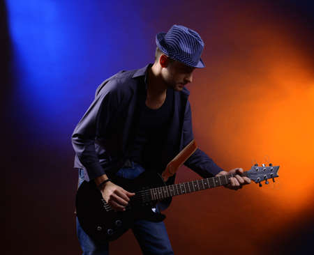 Young musician playing  guitar on dark color background photo