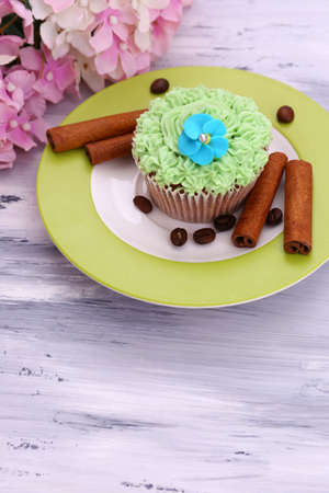 Tasty cupcake with butter cream, on plate, on color wooden background photo