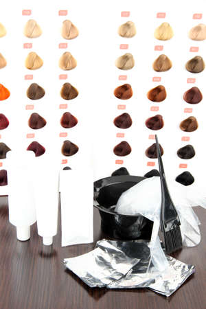 Hair dye kit and hair samples of different colors, on wooden table, on light background photo