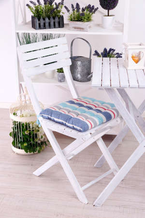 Garden chair and table with flowers on shelves on white background photo