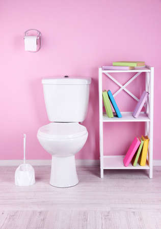 White toilet bowl and stand with books, on color wall background photo