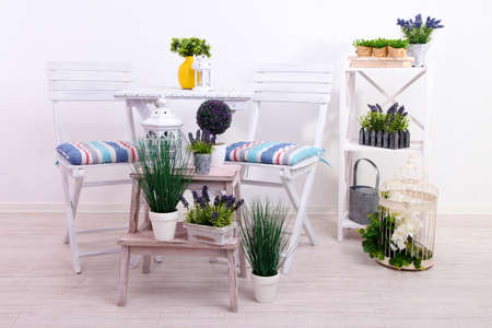 Garden chairs and table with flowers on wooden stands on white background photo
