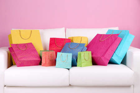 Colorful shopping bags on sofa, on color wall background Stock Photo