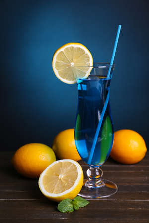 Glass of cocktail on table on dark blue background photo