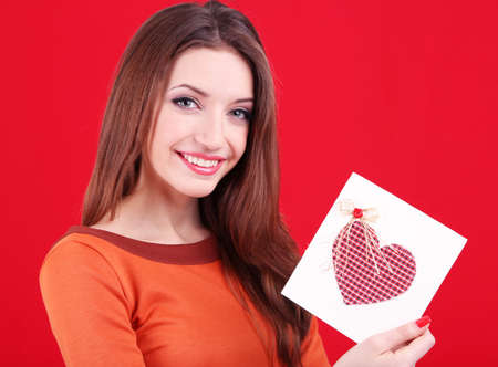 Attractive woman with postcard, on red background photo