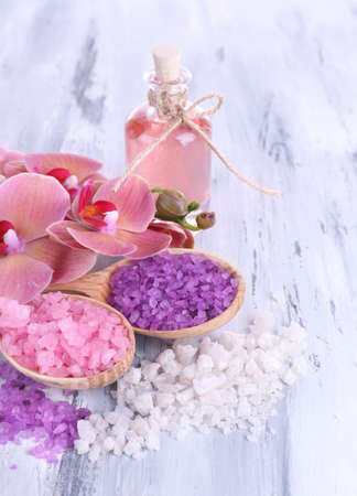Still life with beautiful blooming orchid flower  and wooden spoons with sea salt, on color wooden background photo