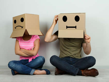 swear: Couple with cardboard boxes on their heads sitting on floor near wall