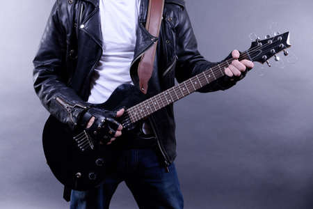 Young musician playing  guitar and singing, on dark color background Stock Photo