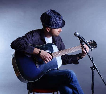 Jonge musicus die akoestische gitaar en zang, op een grijze achtergrond