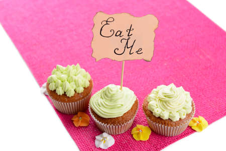 Tasty cupcakes with butter cream,on color napkin, isolated on white photo