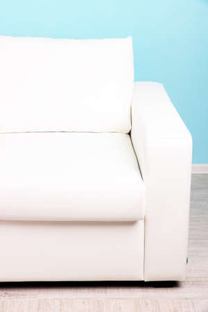 White sofa close-up in room on blue background photo