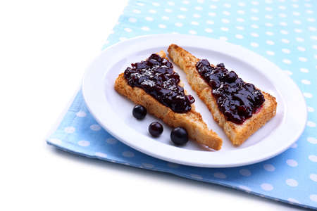 Delicious toast with jam on plate isolated on white photo