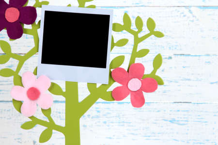 Holder in form of tree with instant photo card on wooden background photo