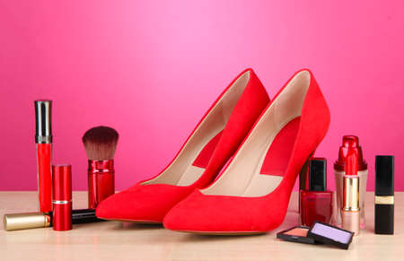 Beautiful red female shoes with cosmetics, on pink background photo