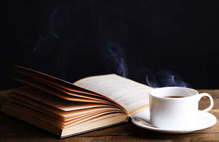 Cup of hot coffee with book on table on dark background