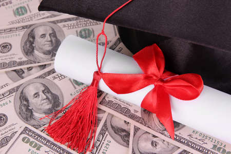Graduation hat and scroll on money background photo