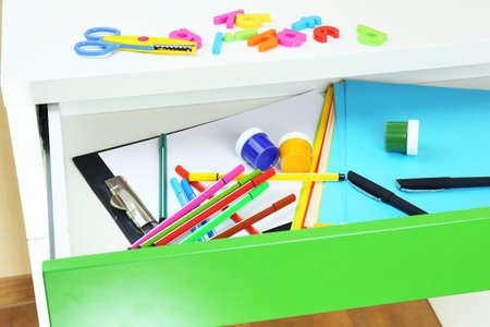 School supplies in open desk drawer close up photo