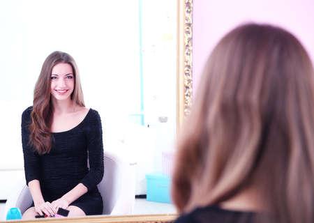 primp: Bella giovane donna seduta davanti allo specchio nella camera