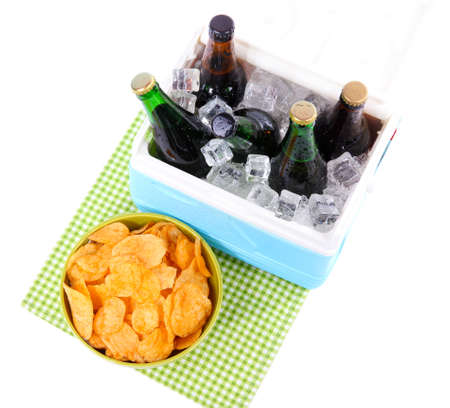 Ice chest full of drinks in bottles on color napkin, isolated on white photo