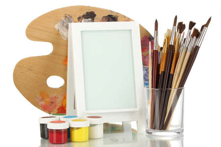 Photo frame as easel with artists tools isolated on white photo