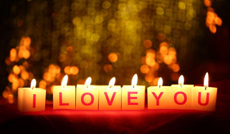 Candles with printed sign I LOVE YOU,on  blur lights background photo