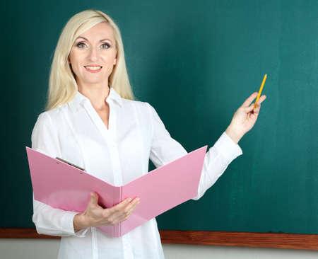 board room: School teacher with folder near blackboard in classroom