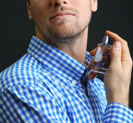 perfume spray: Handsome young man using perfume on black background