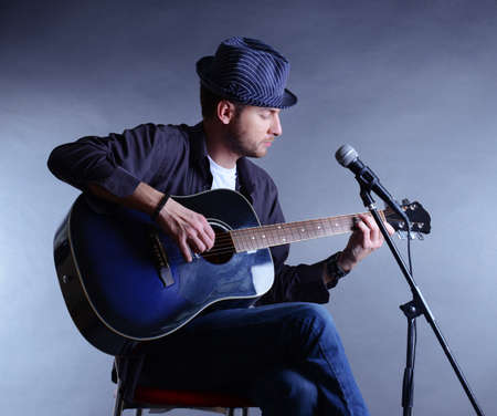 Young musician playing acoustic guitar and singing, on gray background