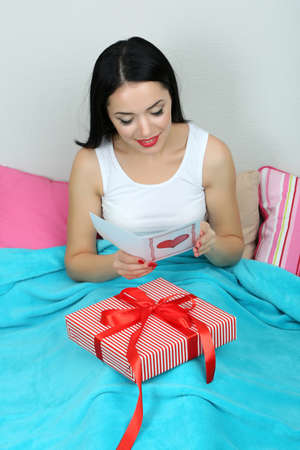 Beautiful woman with gift in bed on Valentine Day photo