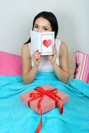 recieve: Beautiful woman with gift in bed on Valentine Day