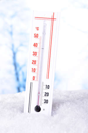 Thermometer in snow on light background photo