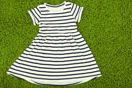 Beautiful dress for little girl  on green carpet photo
