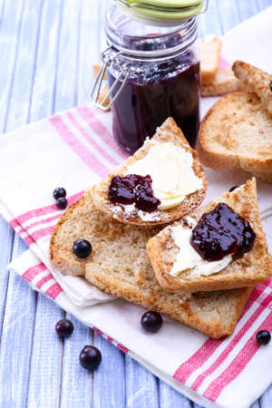 Delicious toast with jam on table close-up photo