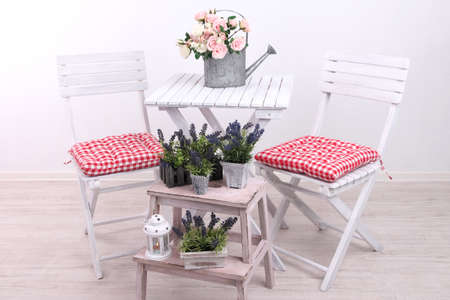 Garden chairs and table with flowers on wooden stand on white background photo