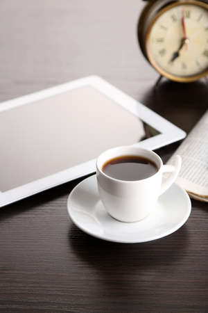 Tablet, newspaper, cup of coffee and alarm clock on wooden table photo