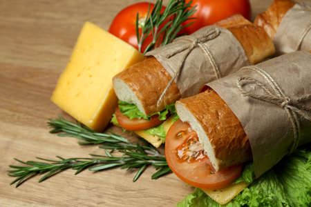 Fresh and tasty sandwich on wooden background photo
